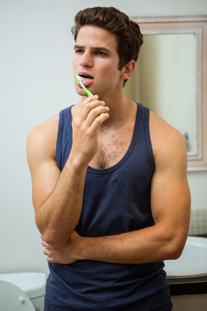 domicile: Young man brushing his teeth in bathroom