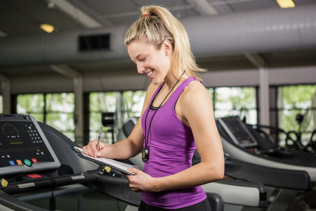 adult  body writing: Trainer writing on clipboard in gym