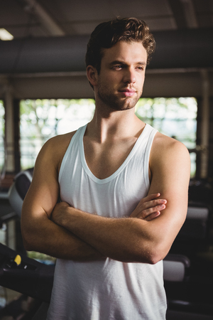 mani incrociate: Handsome man standing in gym with hands crossed