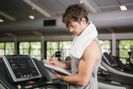 adult  body writing: Gym instructor writing on clipboard in gym