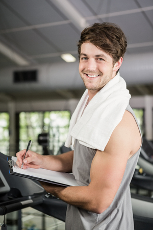 adult  body writing: Portrait of gym instructor writing on clipboard at gym