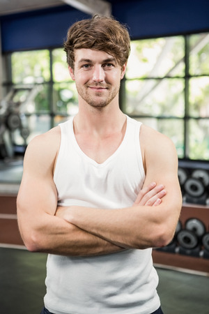 mani incrociate: Portrait of handsome man standing in gym with hands crossed