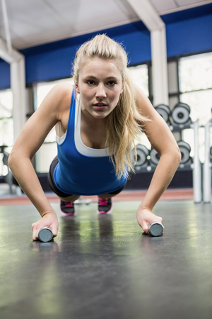 ups: Determined woman doing push ups at gym Stock Photo