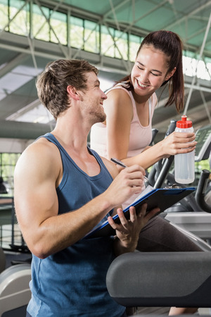 eliptica: Trainer writing on a clipboard while woman exercising on a elliptical machine at gym Foto de archivo