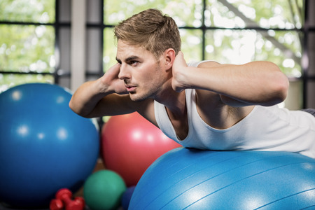 fitness ball: Man working out on a fitness ball at gym