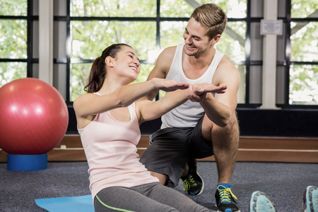 motivating: Trainer motivating a woman while doing crunches at gym Stock Photo