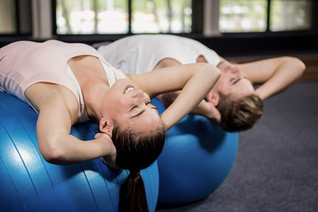 crunches: Man and woman doing abdominal crunches on fitness ball at gym