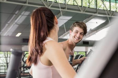 eliptica: mujer feliz y un hombre que ejercita en la máquina elíptica en el gimnasio