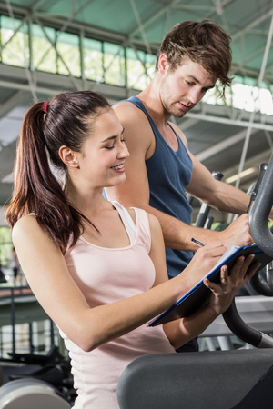 eliptica: Trainer writing on a clipboard while man exercising on a elliptical machine at gym