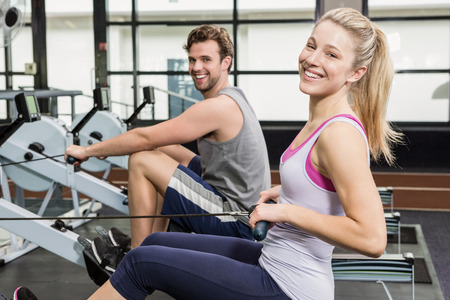 Portrait of a man and woman working out on rowing machine at gym Stock fotó
