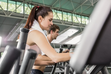eliptica: Woman and man exercising on the elliptical machine at gym