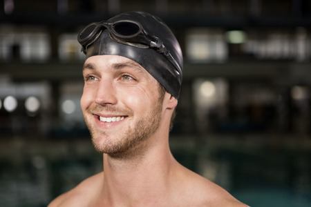 swimming goggles: Swimmer wearing swimming goggles and cap by pool side