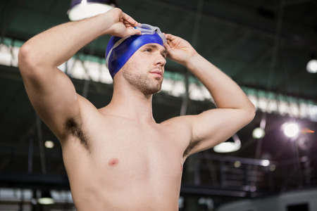 swimming goggles: Confident swimmer wearing swimming goggles and cap by pool side Stock Photo