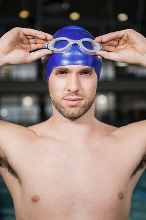 swimming goggles: Portrait of a swimmer wearing swimming goggles and cap by pool side