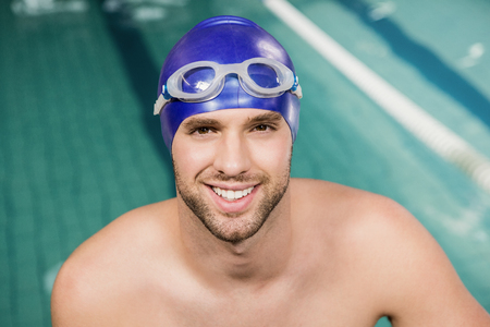 pool side: Portrait of swimmer wearing swimming goggles and cap by pool side
