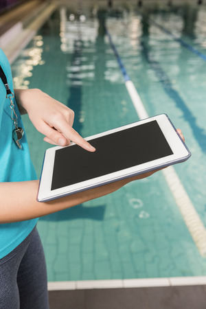 pool side: Mid section of coach using digital tablet by pool side at leisure center