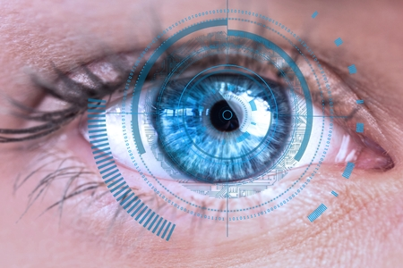 Digital composite of Eye scanning a futuristic interface