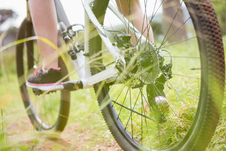 adventuring: Close-up of woman cycling in the countryside LANG_EVOIMAGES