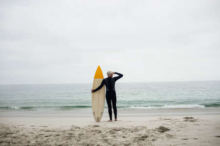 shielding: Senior man with surfboard shielding eyes at beach on a sunny day