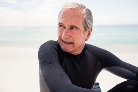 wetsuit: Happy senior man in wetsuit sitting on beach and looking away LANG_EVOIMAGES