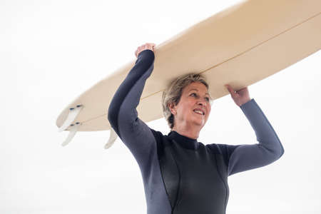 wetsuit: Senior woman in wetsuit carrying surfboard over head on the beach