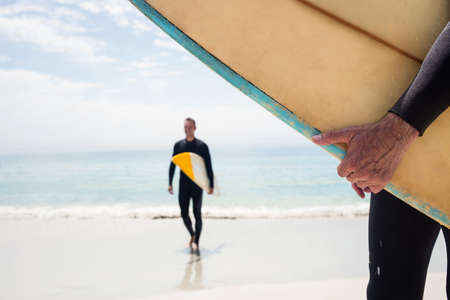 escapism: Man walking with surfboard on the beach on a sunny day