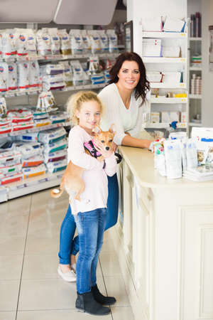 mum and child: Mother and daughter standing with dog at counter in pharmacy