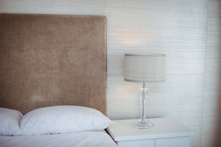 white pillow: Illuminated lamp shade by bed in room