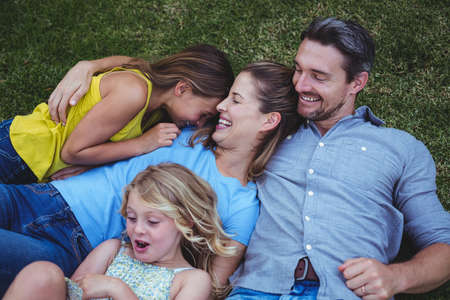 back yard: High angle view of happy family laughing while lying on field in back yard