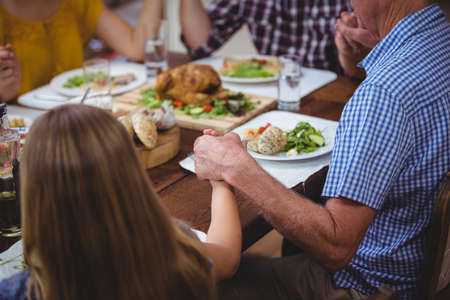family praying: Family holding hands while praying at dining table