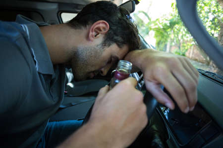 life threatening: Drunk man holding alcohol bottle while sitting in car