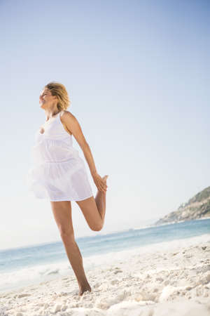 maxi dress: Blonde woman relaxing on the beach on a sunny day