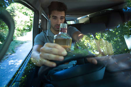drinking driving: Slumped man drinking alcohol while driving car LANG_EVOIMAGES