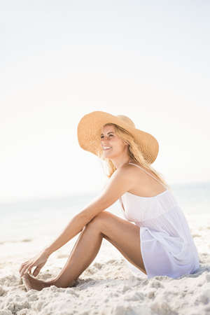 maxi dress: Blonde woman sitting on sand at the beach
