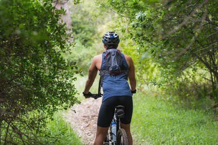 dirt road recreation: Rear view of biker on dirt road amidst trees in forest