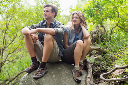 adventuring: Couple relaxing on rock while looking away in forest