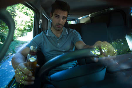 life threatening: Portrait of slumped man holding alcohol bottle while driving car