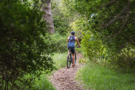 dirt road recreation: Rear view of man riding bicycle  on dirt road amidst trees in forest LANG_EVOIMAGES
