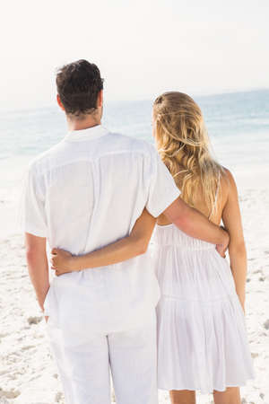 arm around: Couple with arm around each other at the beach LANG_EVOIMAGES