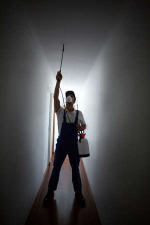 crop sprayer: Front view of manual worker spraying on ceiling in hallway at home LANG_EVOIMAGES