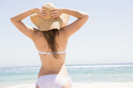 escapism: Blonde woman posing on the beach on a sunny day LANG_EVOIMAGES