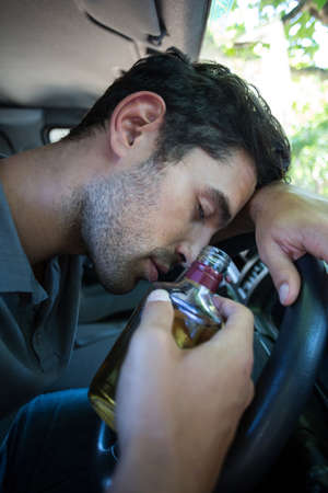 slumped: Close-up of slumped man holding alcohol bottle while sitting in car LANG_EVOIMAGES