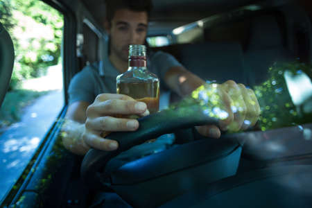 life threatening: Drunk man drinking alcohol bottle while driving car