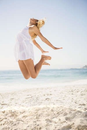 maxi dress: Blonde woman jumping on the beach on a sunny day