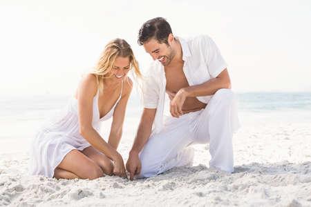 maxi dress: Couple having fun on the beach on a sunny day