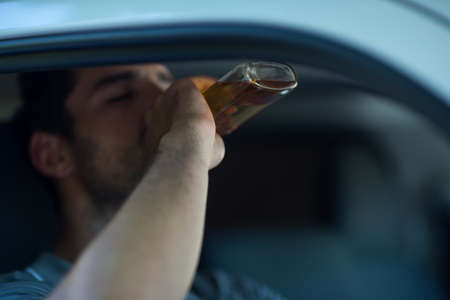 life threatening: Man drinking alcohol while sitting in car