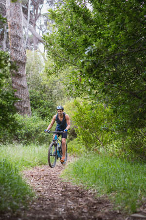 dirt road recreation: Young man riding cycle amidst trees in forest