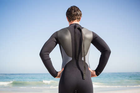 wet suit: Man in wet suit relaxing on the beach