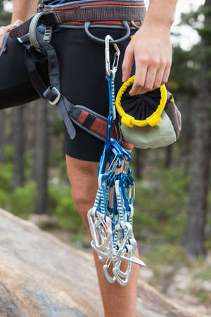 adventuring: Midsection of woman holding climbing equipment on rock at forest