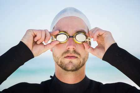 swimming cap: Handsome man wearing swimming cap and goggles on the beach LANG_EVOIMAGES